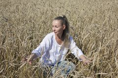 Beautiful woman dress in the field of ripe ears of cereals Royalty Free Stock Image