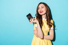 Beautiful woman in dress holding vintage camera and looking away. Portrait of a smiling beautiful woman in dress holding vintage camera and looking away isolated Royalty Free Stock Photos