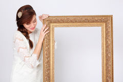 Beautiful woman in dress holds big gilt frame. Beautiful smiling woman in white dress holds big gilt frame and looks down at frame royalty free stock photo