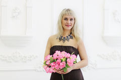 Beautiful woman in dress holds flowers Royalty Free Stock Images