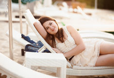 Beautiful woman in dress lying on sunbed at beach Royalty Free Stock Images
