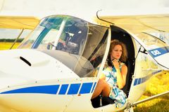 Beautiful woman in dress the pilot in a cockpit of the ultralight plane Stock Photos