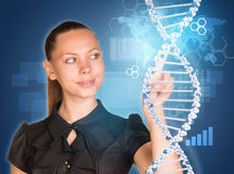 Beautiful woman in dress pointing finger on DNA Royalty Free Stock Photos