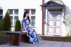 Beautiful woman in dress sitting on the bench in old town of Tal. Young beautiful woman in dress sitting on the bench in old town of Tallinn, Estonia Stock Images