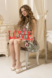 Beautiful woman in a dress sitting on a chair Royalty Free Stock Photo