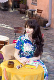 Beautiful woman in dress sitting in summer cafe Stock Photography