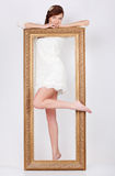 Beautiful woman in dress stands behind big gilt frame Royalty Free Stock Photo