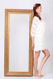 Beautiful woman in dress stands near big gilt frame. Beautiful young woman in white dress stands near big gilt frame and propped it by back stock photos