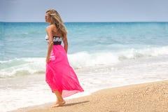 Beautiful woman in a dress walking on the beach.Relaxed woman breathing fresh air,emotional sensual woman near the sea, enjoying s stock photography