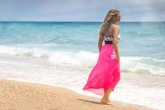 Beautiful woman in a dress walking on the beach.Relaxed woman breathing fresh air,emotional sensual woman near the sea, enjoying s stock photos