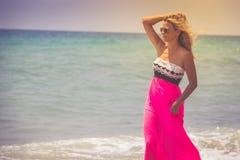 Beautiful woman in a dress walking on the beach.Relaxed woman breathing fresh air,emotional sensual woman near the sea, enjoying s stock image