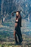 Beautiful woman dressed as a fairy witch in raincoat and with horns for Halloween royalty free stock images