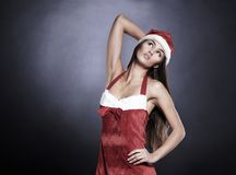 Beautiful woman dressed as Santa Claus posing for the camera. Isolated on a black background Stock Image