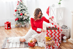 Beautiful woman dressed as Santa looks a gift Royalty Free Stock Photography