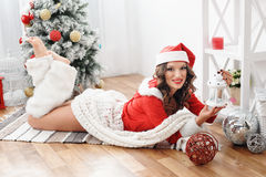 Beautiful woman dressed as Santa near the Christmas tree Stock Image