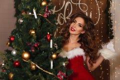 Beautiful woman dressed as Santa near the Christmas tree Royalty Free Stock Photos