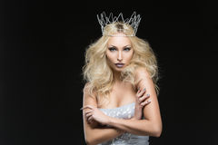 Beautiful woman dressed as winter queen. Beautiful young woman in crown and silver top over black background. Winter queen. Copy space Stock Images