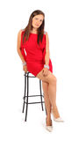 Beautiful woman dressed in dress sits on stool Royalty Free Stock Images