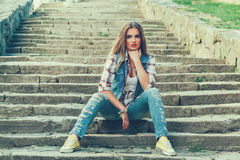 Beautiful woman dressed in jeans posing on a concrete stai Stock Photo