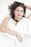 Beautiful woman dressed in white on bed Stock Image