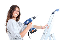 Beautiful woman with a drill on a ladder. Ready to use it Stock Images