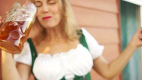 A beautiful woman is drinking beer at the Oktoberfest festival. White-toothed smile, red lips