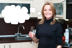 Beautiful happy smiling woman in kitchen interior drinking champ Stock Photography