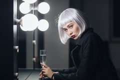 Beautiful woman drinking champaigne in dressing room. Beautiful serious young woman drinking champaigne near the miror in dressing room Royalty Free Stock Images