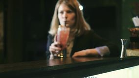 Beautiful woman drinking a cocktail at the bar 4k stock video