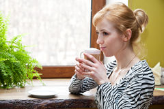 A beautiful woman is drinking coffee Stock Photos