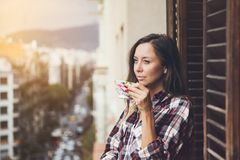 Beautiful woman is drinking coffee on a balcony and enjoying the city view. Close up of a woman holding in hands cup of coffee. Early morning routine. Sun light Stock Images