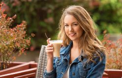 Beautiful woman drinking coffee. One the street royalty free stock photos