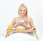 Beautiful woman drinking coffee in bed Stock Photos