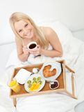 Beautiful woman drinking coffee in bed Stock Image
