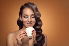 Portrait of beautiful woman drinking coffee on brown background. Beautiful woman drinking coffee on brown background Stock Photography