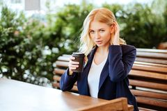 Woman drinking coffee in a cafe royalty free stock photos