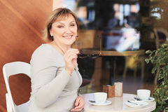 Beautiful woman is drinking coffee in the cafe. Stock Photo