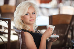 Beautiful woman drinking coffee in cafe restaurant, girl in bar, summer vacation. Pretty blond at breakfast. happy smiling woman Royalty Free Stock Photo