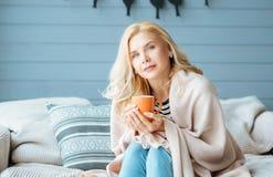Beautiful woman drinking coffee in cozy bedroom Stock Image