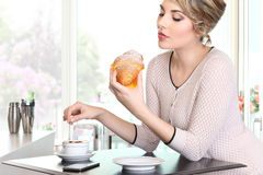 Beautiful woman drinking coffee with croissant in a cafe Stock Image