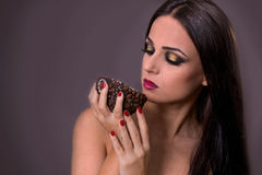 Beautiful woman drinking coffee from a special mug. Beautiful woman with dark hair and fancy makeup drinking coffee from a special mug covered with coffee beans Royalty Free Stock Photo