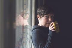 Beautiful Woman Drinking Coffee in Dark Room Stock Photography