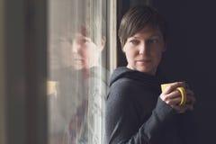 Beautiful Woman Drinking Coffee in Dark Room Stock Photo