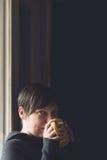 Beautiful Woman Drinking Coffee in Dark Room Stock Images