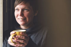 Beautiful Woman Drinking Coffee in Dark Room Stock Images