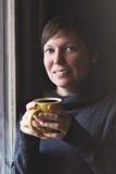 Beautiful Woman Drinking Coffee in Dark Room Stock Image