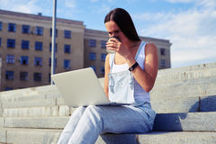 Beautiful woman drinking coffee and holding laptop on her knees. Beautiful woman in casual clothes is drinking coffee and holding laptop on her knees against royalty free stock photo