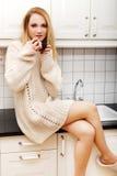 Beautiful woman drinking coffee in the kitchen. Stock Photo