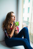 Beautiful young woman drinking coffee and looking through window while sitting at windowsill at home Royalty Free Stock Images
