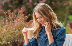 Beautiful woman drinking coffee. One the street royalty free stock photography